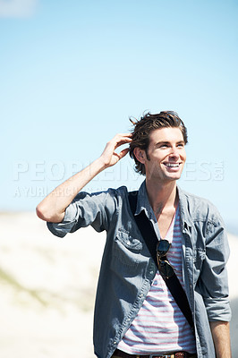Buy stock photo Handsome young man in a denim shirt smiling and touching his head with dunes and sky in the background