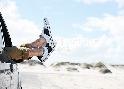 Buy stock photo Cropped image of two feet wearing sneakers sticking out of a parked car window with dunes in the background