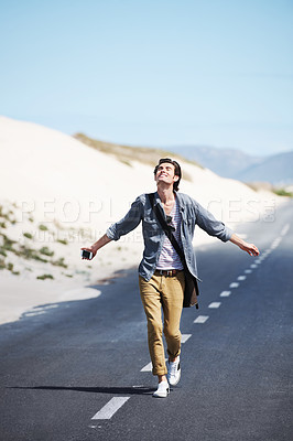Buy stock photo Handsome young man with his arms outstretched walking down an empty road
