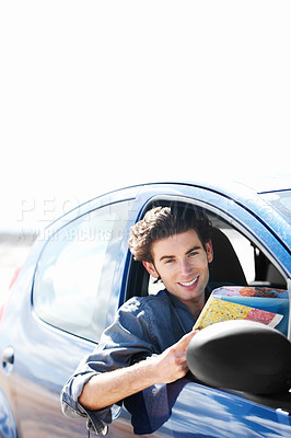 Buy stock photo Young man sitting in his car ands smiling at the camera while holding a map