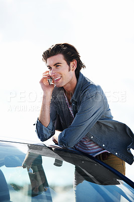 Buy stock photo Happy young man leaning on the roof of his car while smiling and speaking on his cellphone
