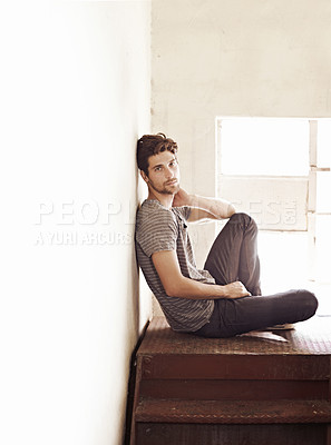 Buy stock photo Young man sitting and contemplating his future on a stairwell