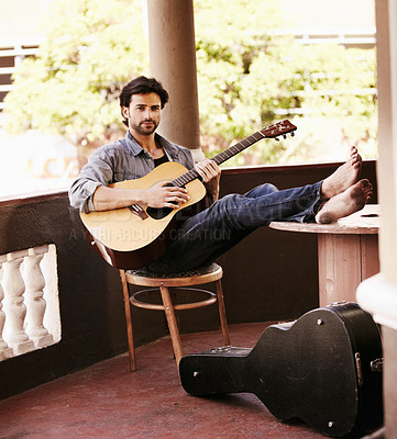 Buy stock photo Handsome young man sitting and playing the guitar while on the verandah