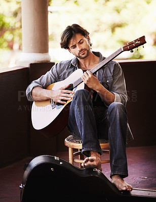 Buy stock photo Handsome young man sitting and playing the guitar