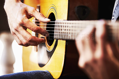 Buy stock photo Cropped view of masculine hands strumming a guitar