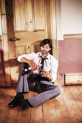 Buy stock photo Drunk young business executive sitting in a doorway pouring himself a drink