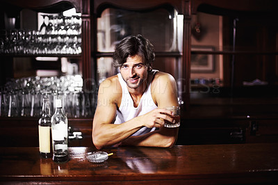 Buy stock photo Handsome young barman enjoying a cigarette and a drink
