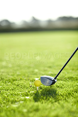Buy stock photo A golf club lining up to tee-off with a yellow ball on a golf course
