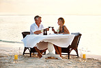 Romantic couple celebrating with wine at the beach