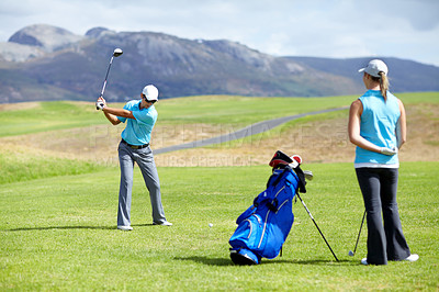 Buy stock photo A young male golfer taking a few practice swings before driving his ball down the fairway