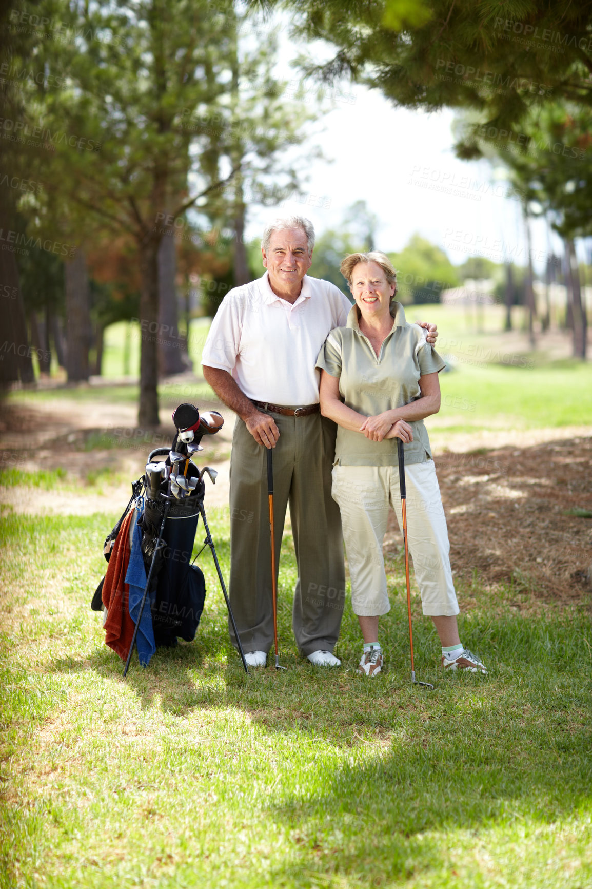 Buy stock photo Portrait of a mature, happy couple standing together smiling on a golf course