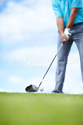 Buy stock photo Cropped image of a young male golfer teeing up to play a shot with his driver