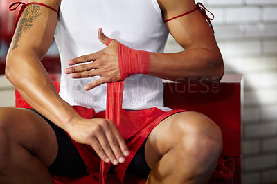 Buy stock photo Cropped image of a young fighter wrapping his hands