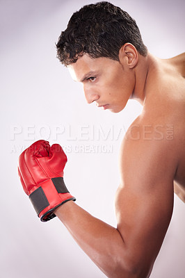 Buy stock photo A handsome young fighter pulling his bicep on a white background
