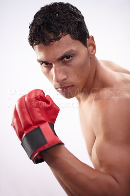 Buy stock photo Portrait of a handsome young fighter pulling his bicep on a white background