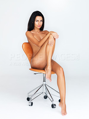 Buy stock photo A studio portrait of an attractive nude woman seated on a chair with her hands on her knee