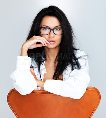 Buy stock photo A studio portrait of an attractive model seated in a chair and wearing glasses