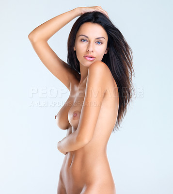 Buy stock photo A side view studio portrait of a beautiful naked model with one arm around her waist and the other touching the top of her head
