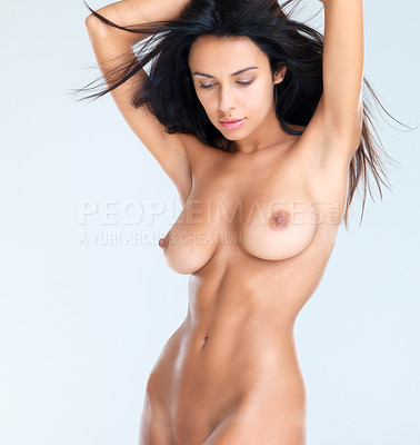 Buy stock photo A studio shot of a beautiful naked model with her arms raised above her head