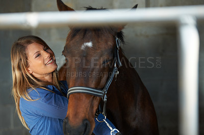 Buy stock photo A young woman smiling as she brushes her horse in the stable