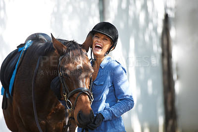 Buy stock photo A beautiful woman laughing outside while standing outside with her horse