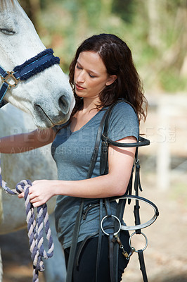 Buy stock photo An attractive woman holding a bridle while outside with her horse