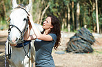 Attaching the bridle to her horse