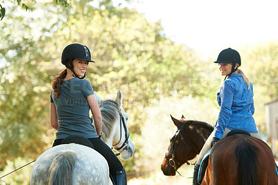 Buy stock photo Rear view of two young women on horseback looking back at the camera