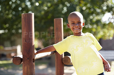 Buy stock photo Portrait, of smiling african american boy leaning against a piece fo wooden fence outside