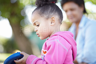 Buy stock photo A side view of  a pre-school ethnic girl looking down at a bug with interest