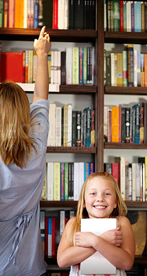 Buy stock photo A cute young girl clutching her book in a library