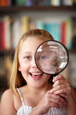 Buy stock photo A little blonde girl looking through a magnifying glass
