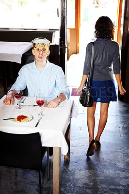 Buy stock photo A woman walking away from an unhappy man with spaghetti on his head