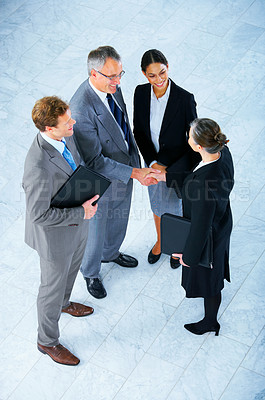 Buy stock photo Handshake and teamwork. A group of business people shaking hands in a light and modern office.