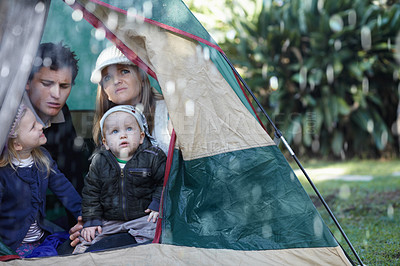 Buy stock photo Young family stuck in their tent during a rainy day