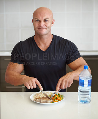 Buy stock photo Portrait of a muscular man eating a well-balanced meal at his kitchen counter