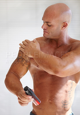 Buy stock photo A muscular man applying a lotion to his skin