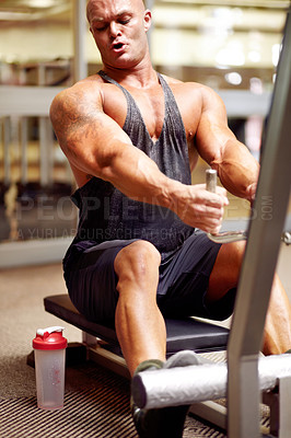Buy stock photo Shot of a male bodybuilder using an exercise machine at the gym