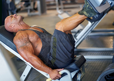 Buy stock photo Shot of a male bodybuilder doing leg exercises on a machine at the gym
