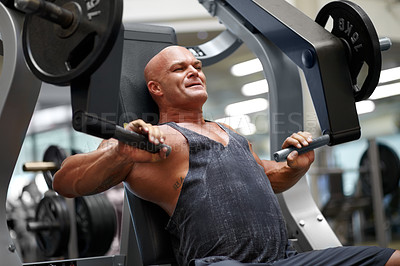 Buy stock photo Shot of a male bodybuilder using exercise equipment at the gym
