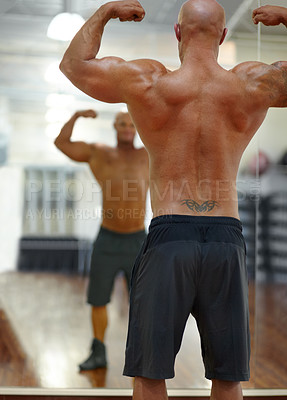 Buy stock photo Rearview shot of a male bodybuilder flexing his muscles at the gym in front of the mirror
