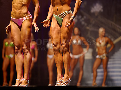 Buy stock photo Female body building contestants flexing their muscles for the judges