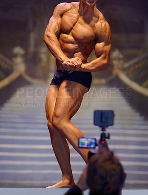 Buy stock photo Rearview of a cameraman filming a bodybuilder flexing his muscles during a competition