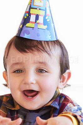 Buy stock photo Shot of a cute little boy wearing a party hat looking excited