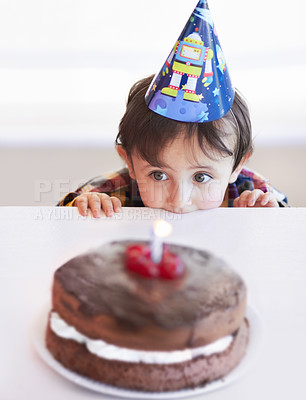 Buy stock photo A cute little boy looking at his birthday cake in anticipation