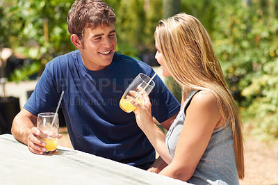 Buy stock photo A young couple sitting outside and drinking orange juice