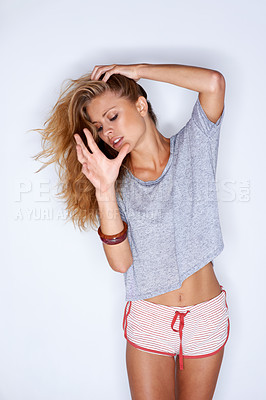 Buy stock photo Studio shot of woman in a shirt and shorts touching her hair and looking down