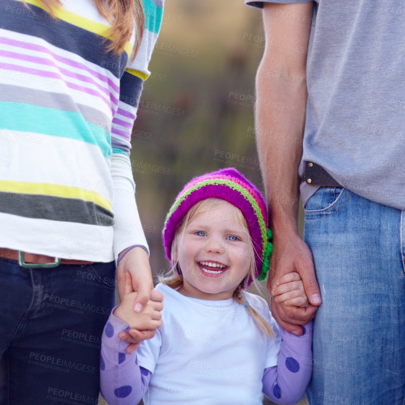 Buy stock photo Portrait of a cute little girl standing in between her mother and father