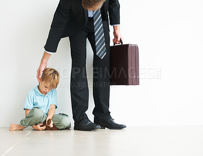 Buy stock photo A young boy holding a teddybear and looking upset because his father has to go to work