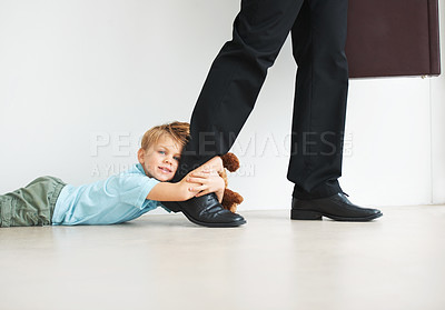 Buy stock photo Portrait of a cute young boy holding onto his dad's leg as he tries to leave for work